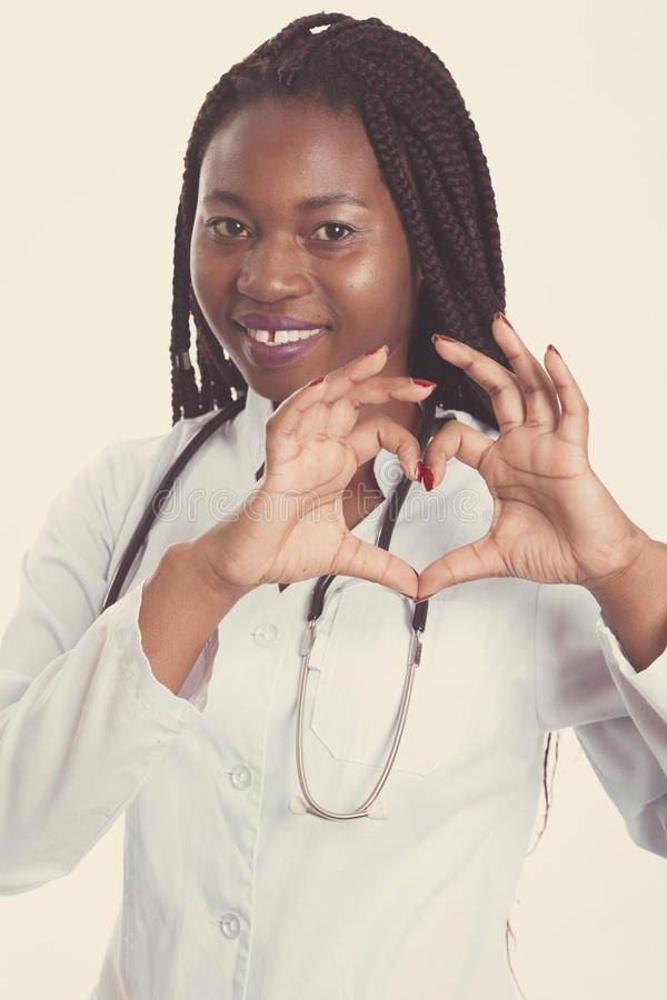 Female american african doctor, nurse woman wearing medical coat with stethoscope doing heart with hands. Happy excited for. Success medical worker posing on royalty free stock photos