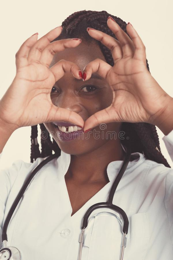 Female american african doctor, nurse woman wearing medical coat with stethoscope doing heart with hands and looking through it. Happy excited for success royalty free stock photo