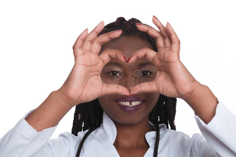 Female american african doctor, nurse woman wearing medical coat with stethoscope doing heart with hands and looking through it. Happy excited for success stock photo