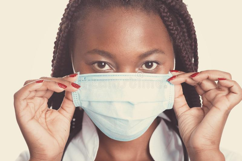 Female american african doctor, nurse woman wearing medical coat with stethoscope and mask. Happy excited for success medical. Worker posing on light background stock image