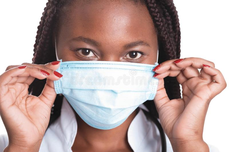 Female american african doctor, nurse woman wearing medical coat with stethoscope and mask. Happy excited for success medical. Worker posing on light background royalty free stock images