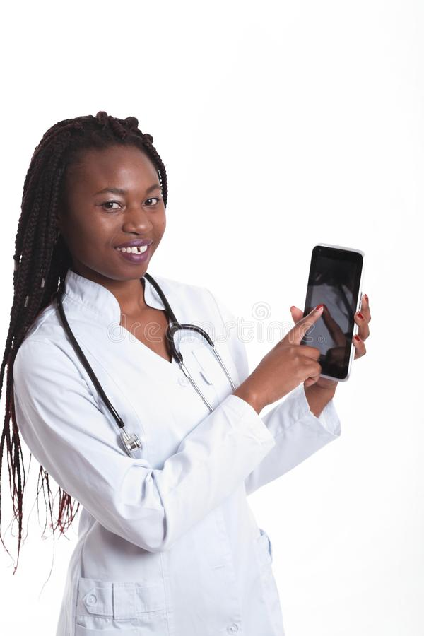 Female american african doctor, nurse woman wearing medical coat with stethoscope show something on tablet. Happy excited for. Success medical worker posing on stock photo