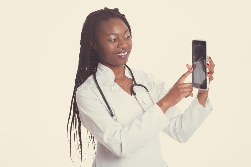 Female american african doctor, nurse woman wearing medical coat with stethoscope show something on tablet. Happy excited for. Success medical worker posing on royalty free stock photography
