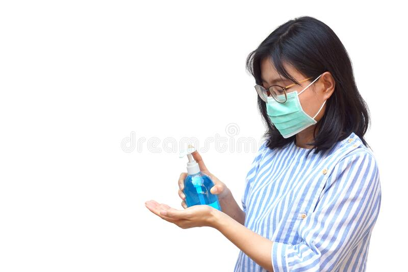 Female applying alcohol gel and wearing medical mask stock image
