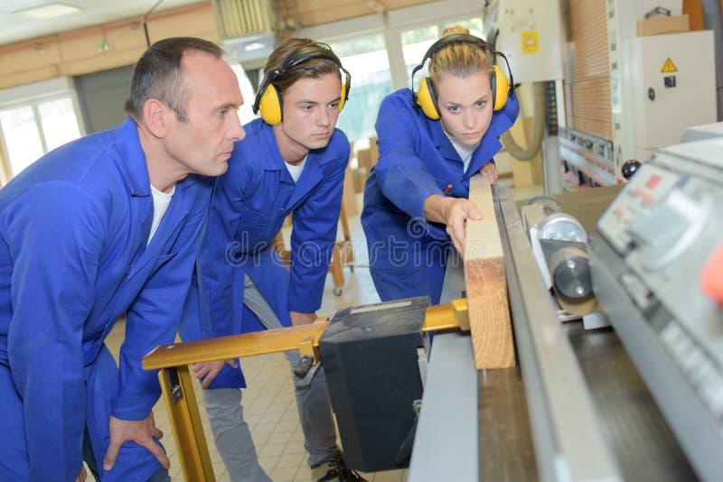 Female apprentice carpenter using machinery royalty free stock photo
