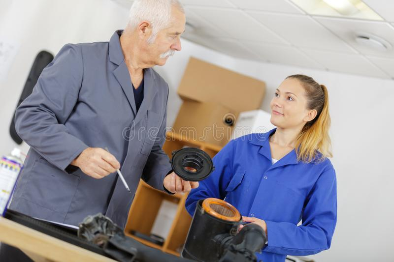 Female apprentice mechanic with teacher looking at parts stock photos
