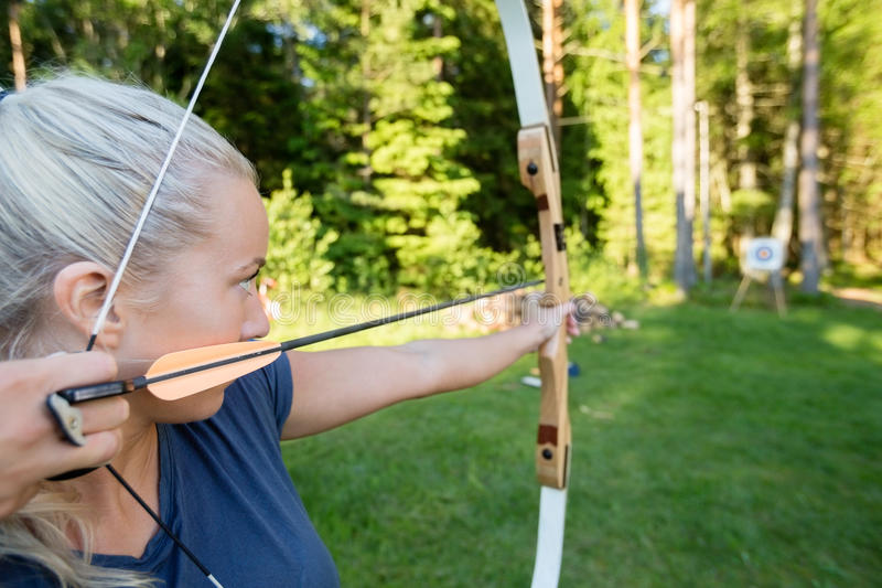 Female Archer Aiming Arrow At Target Board In Forest. Confident young female archer aiming arrow at target board in forest stock photo
