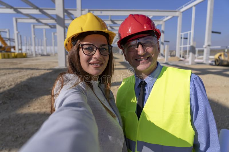 Female Architect and Businessman Taking Selfie Photo with Cell Phone at Construction Site royalty free stock photos