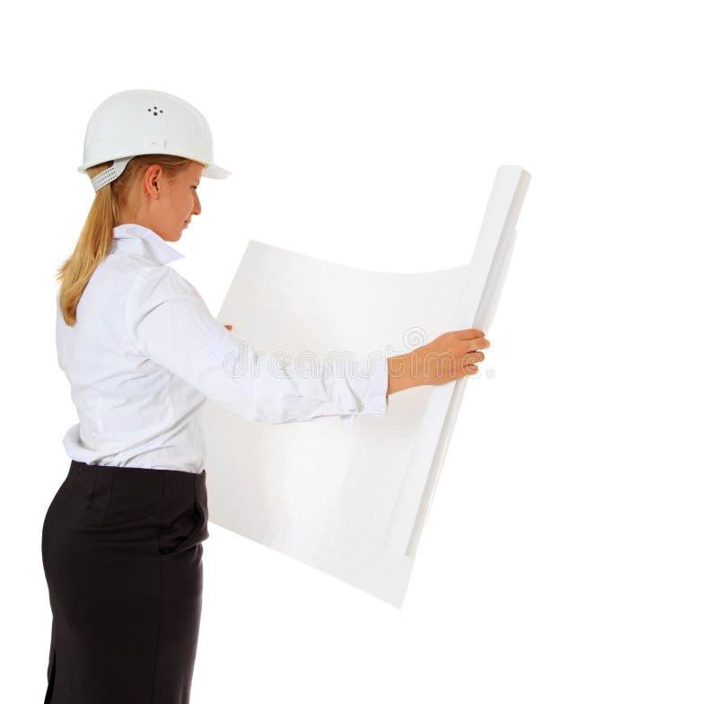 Female architect checking blueprint stock photography