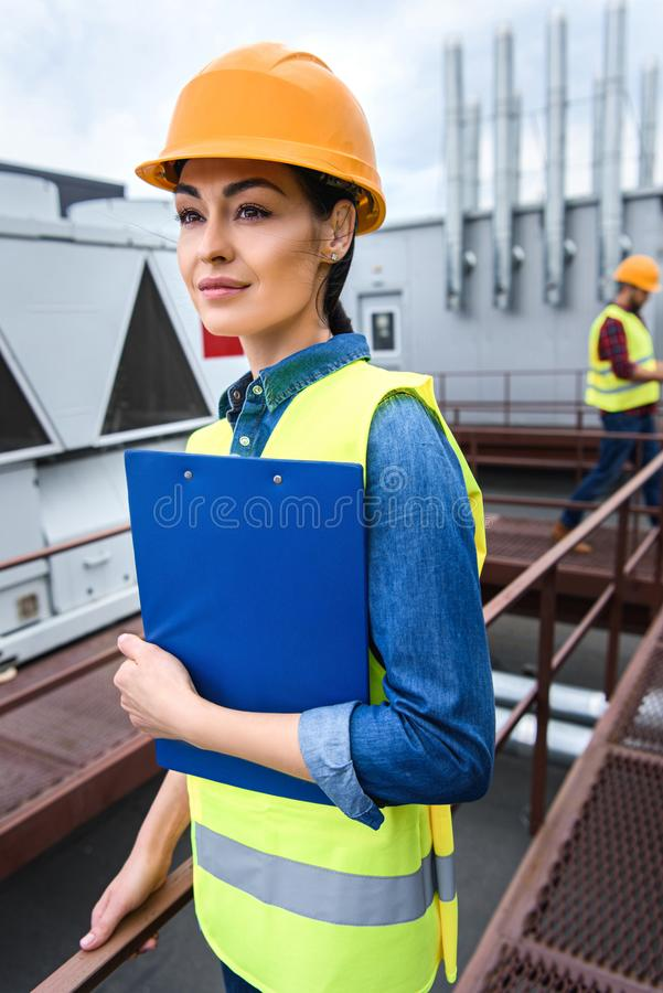 female architect in helmet holding clipboard on roof male stock photo