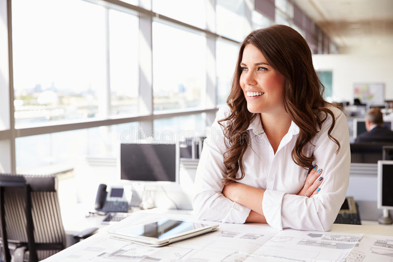 Female architect at her desk in an office, looking away royalty free stock images