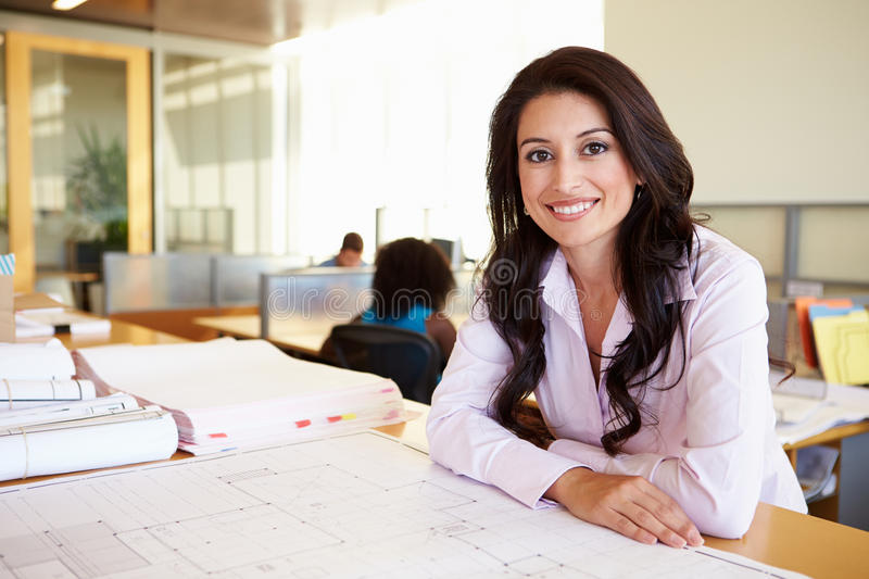 Female Architect Studying Plans In Office royalty free stock photography