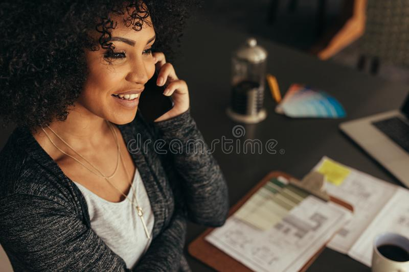 Female architect talking with client over phone. Close up portrait of happy young woman sitting at her desk talking on mobile phone. Female architect talking stock images