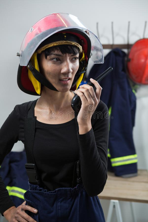 Female architect talking on walkie-talkie. Close-up of female architect talking on walkie-talkie stock image