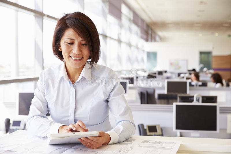 Female architect at work in an office using tablet computer royalty free stock photo