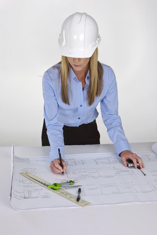 Female architect working on blue prints royalty free stock photo