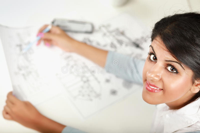 Female architect working with blueprints at office royalty free stock photography