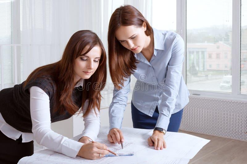 Female architects studying blueprints and make notes royalty free stock photography