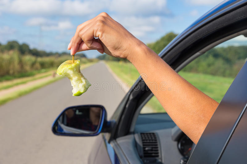 Female arm dropping apple core out car window. Female arm throwing fruit waste out of car window royalty free stock images