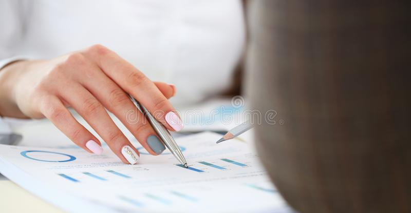 Female arm holding silver pen point in financial graph stock images