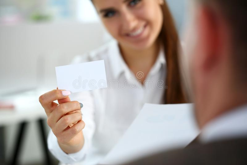 Female arm in suit give blank calling card to visitor. Closeup. White collar colleagues company name exchange job interview sale clerk id executive or ceo stock image