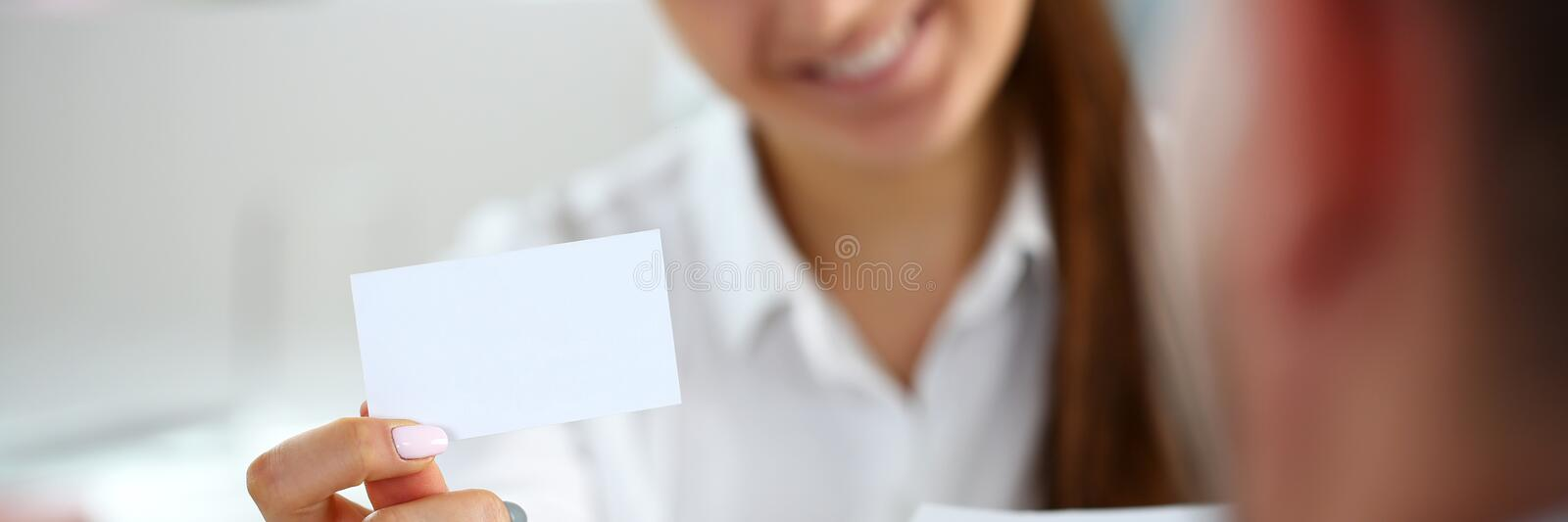Female arm in suit give blank calling card to visitor. Closeup. White collar colleagues company name exchange job interview sale clerk id executive or ceo stock photography