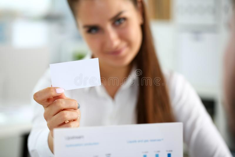 Female arm in suit give blank calling card to visitor. Closeup. White collar colleagues company name exchange job interview sale clerk id executive or ceo royalty free stock photo