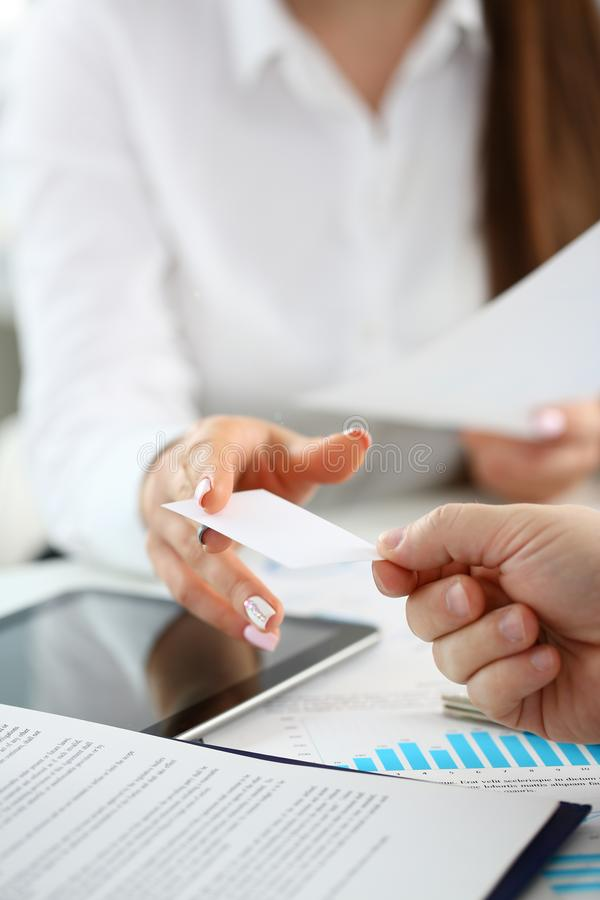 Female arm in suit give blank calling card to visitor. Closeup. White collar colleagues company name exchange job interview sale clerk id executive or ceo stock photo