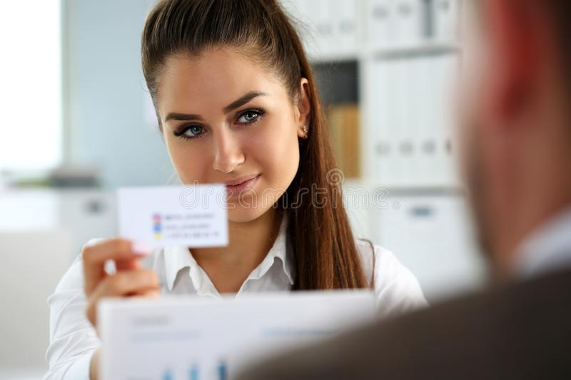 Female arm in suit give blank calling card to visitor. Portrait. White collar colleagues company name exchange job interview sale clerk id executive or ceo stock photography