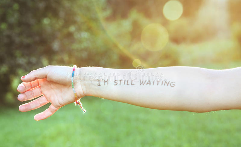 Female arm with text -I'm still waiting- written stock photos