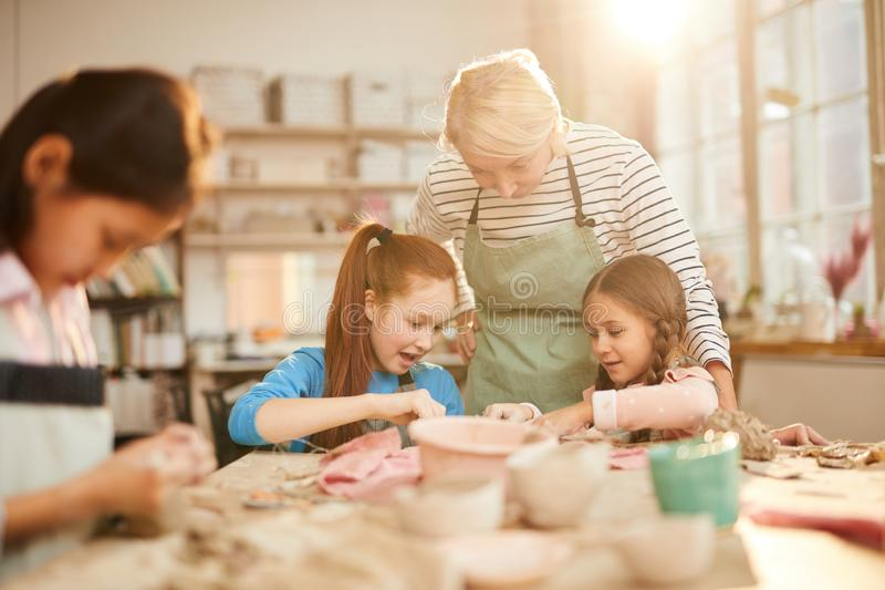Female Art Teacher Working with Kids stock images