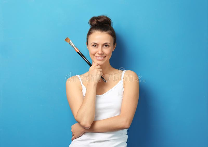 Female artist with brush on color background stock photography