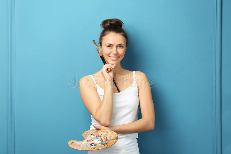 Female artist with brush and paint palette on color background royalty free stock images