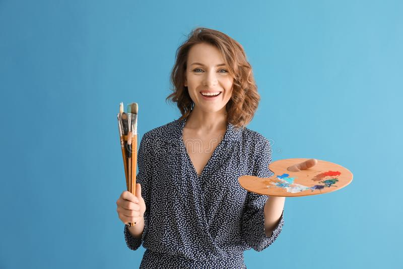 Female artist with brushes and paint palette on color background stock image