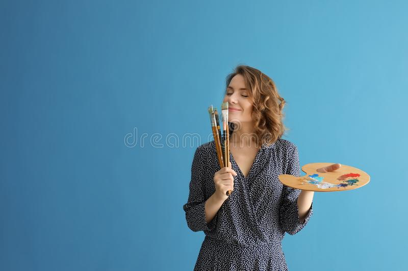 Female artist with brushes and paint palette on color background royalty free stock photography
