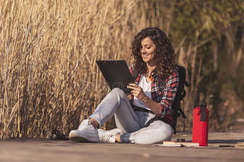 Female artist drawing outdoors. Female artist sitting on the wooden lake docks, enjoying sunny autumn day in nature and drawing in a sketchbook stock photography