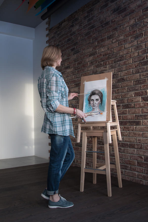 Female artist draws in the room stock photography