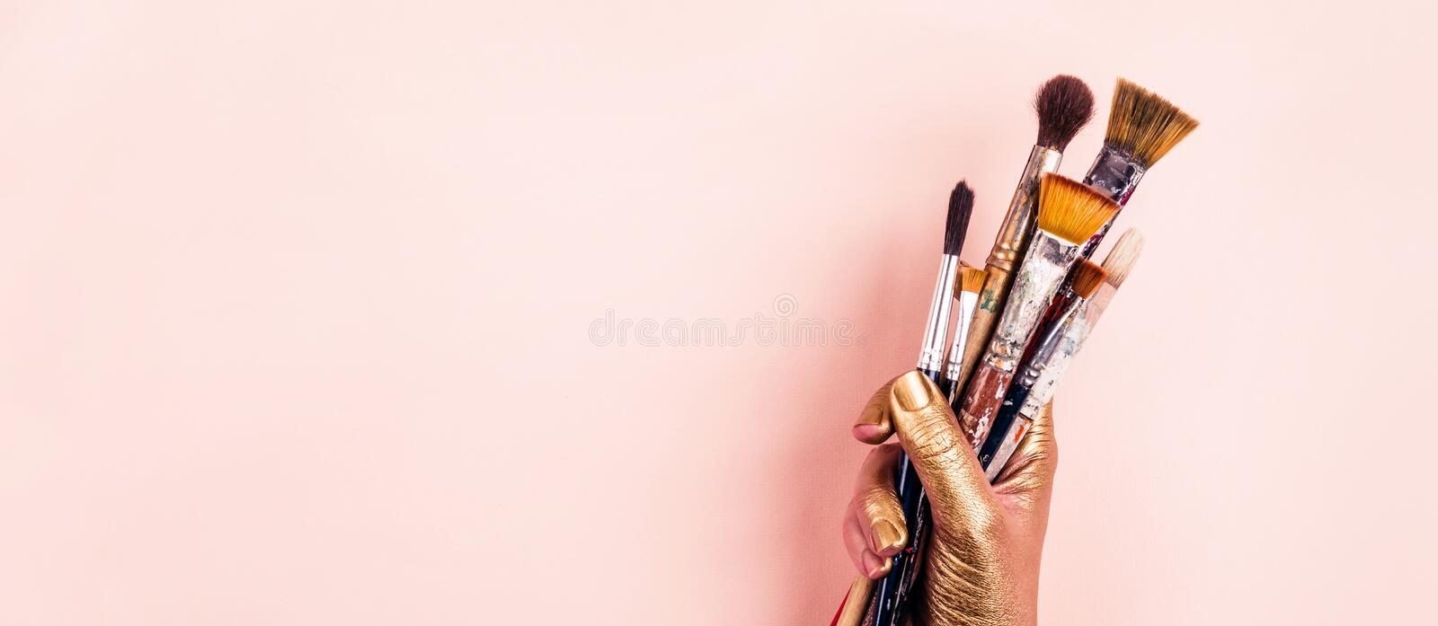 Female Artist golden hand with set of brushes. Banner format royalty free stock photos