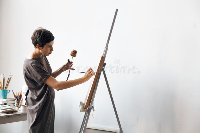 Female artist in her spacious white studio working with watercolor painting. Natural lighting. Disclosure of creativity concept. Horizontal composition with stock image