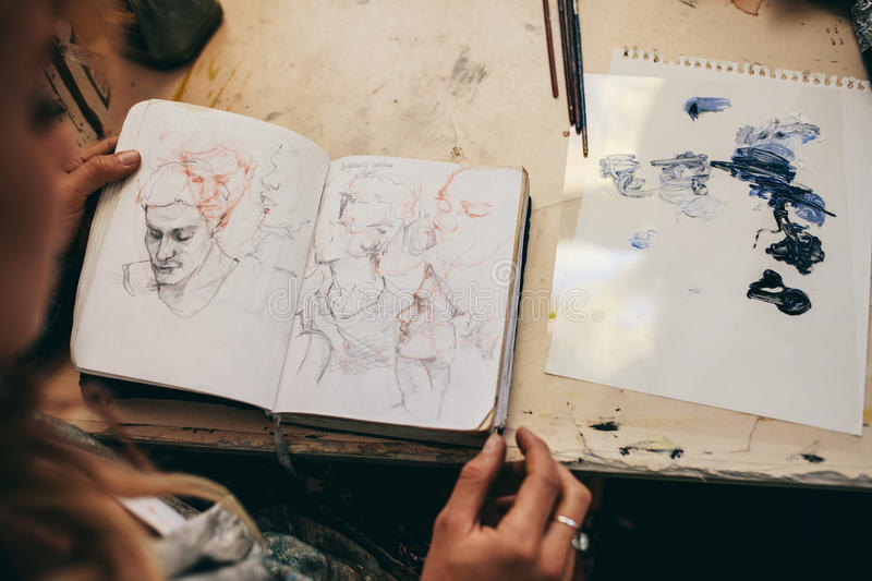 Female artist looking at sketches in her studio stock images