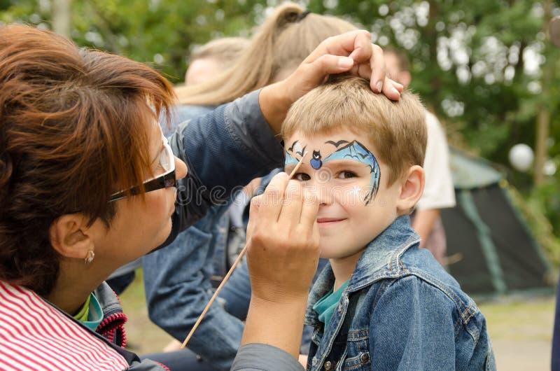 Female artist paints a bat mask on a boy's face stock photography