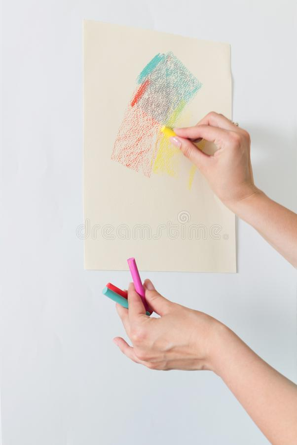Female artist`s hand draw chalk pastel on paper, easel royalty free stock photography