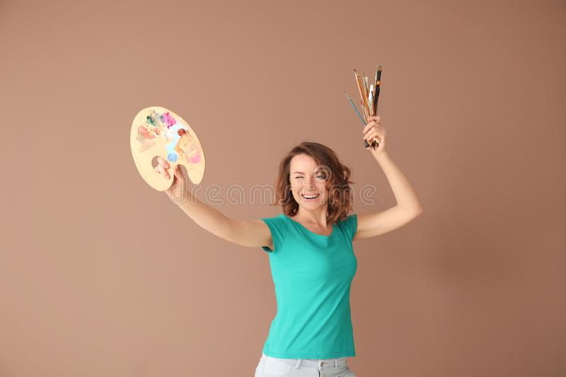 Female artist with tools and paint palette on color background royalty free stock photography