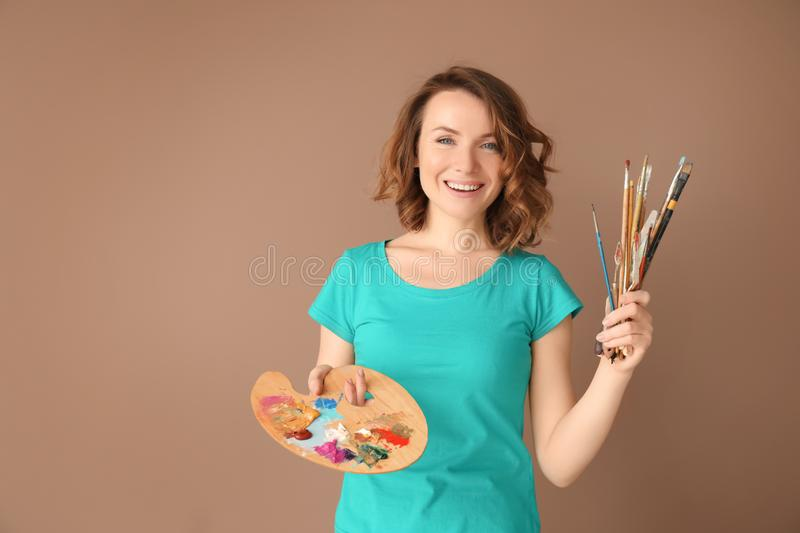 Female artist with tools and paint palette on color background royalty free stock images