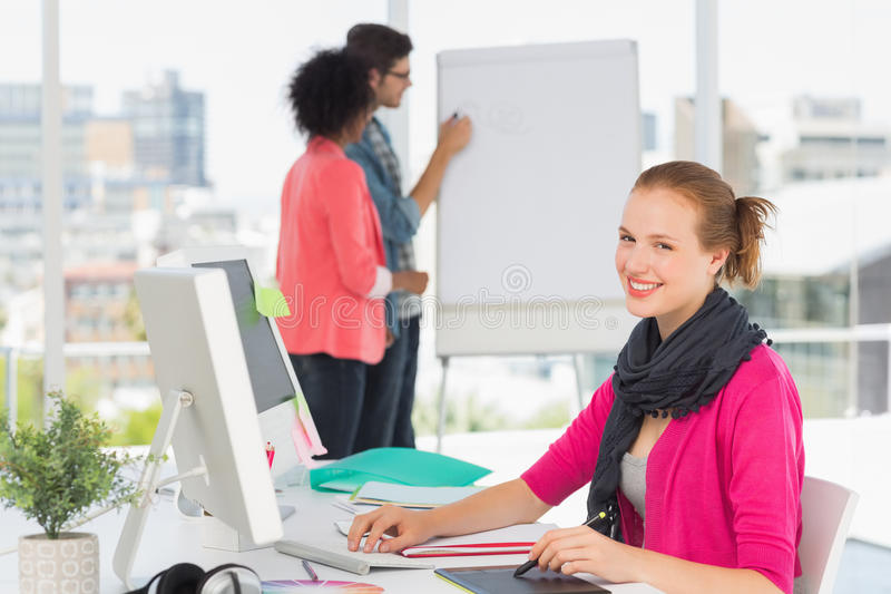 Female artist using graphic tablet with colleagues at office stock photography