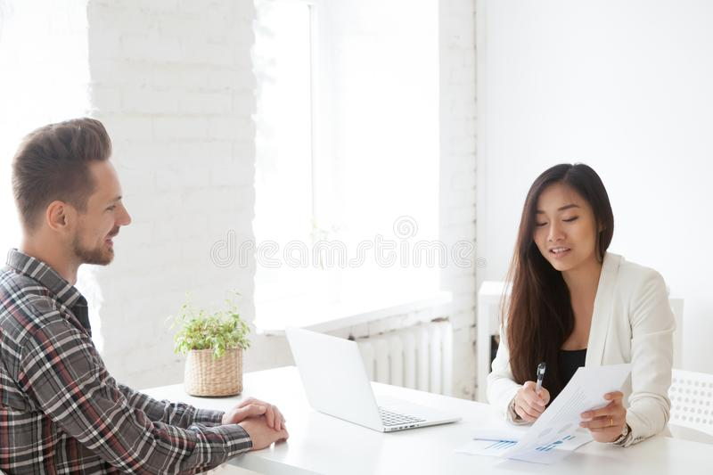 Female Asian employer mentoring male subordinate on financial is royalty free stock images