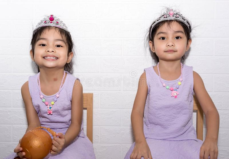 Female asian identical twins sitting on chair with white background. Wearing purple dress and accessories like necklace, crown stock photo
