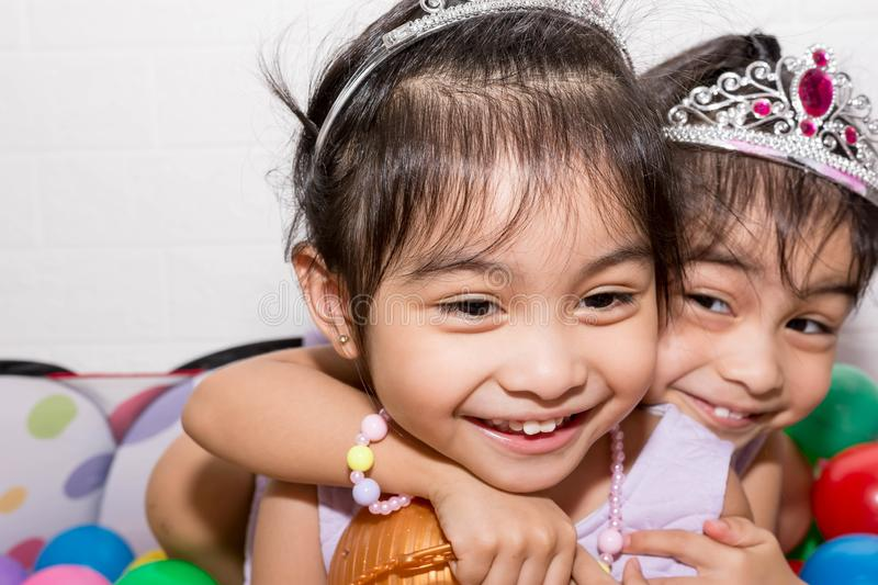 Female asian identical twins sitting on chair with white background. Wearing purple dress and accessories. Playing colorful. Plastic toy balls and kissing and royalty free stock images