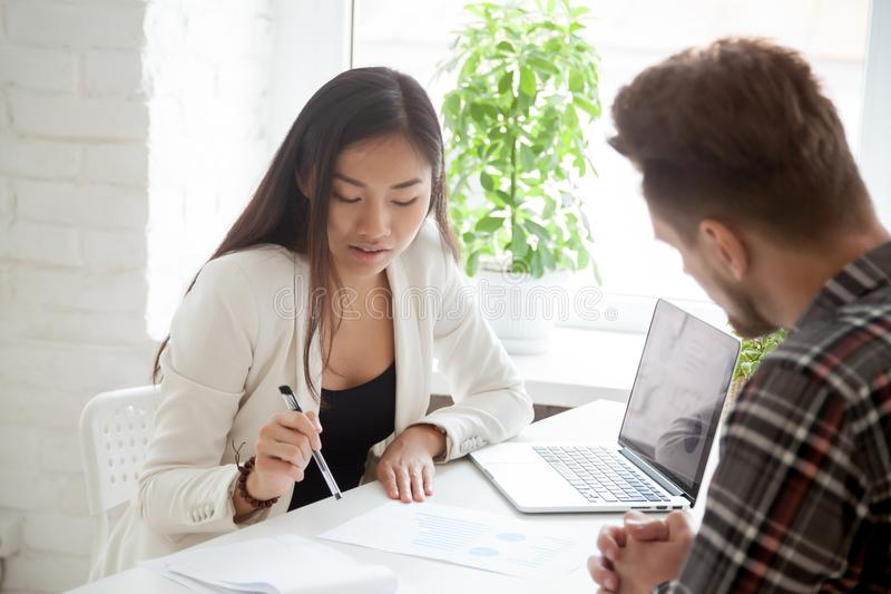 Female Asian supervisor explaining financial graphs to male coll. Eague, talking on business issues, mentor coaching coworker, speaking on finances, partners stock photo