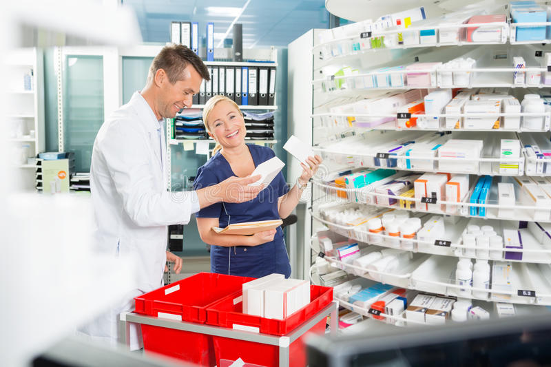 Female Assistant Arranging Products With Male. Portrait of happy female assistant arranging products with male pharmacist in pharmacy royalty free stock photography